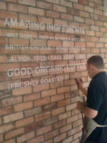 Wayne Osborne Signwriting a display wall sign