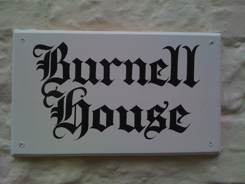 Hand lettered house sign with old english lettering