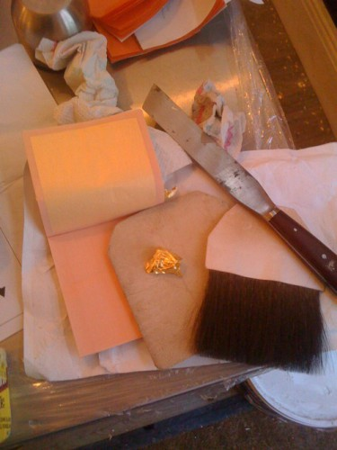 Simple tools used to apply loose gold leaf