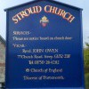 Church notice board with heraldic badge and gold lettering